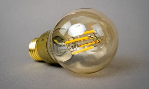 LED Filament Bulb On Its Side, not illuminated with a gold coloured base