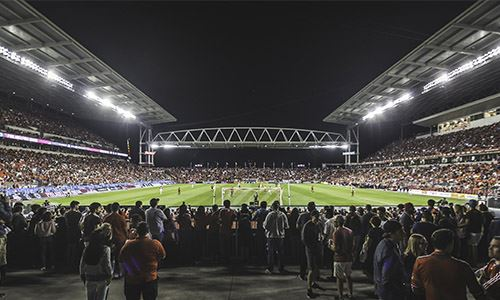 Football stadium filled with fans at night with bright lights illuminating the pitch